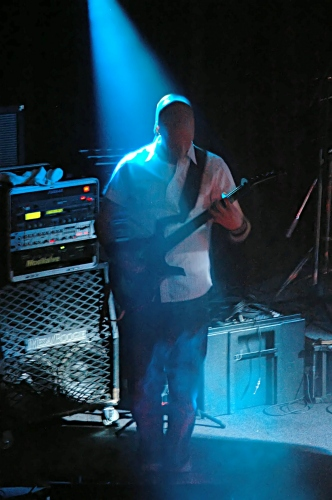 Shot of the guitar player for Counterfist backlit by a blue beam of light.  John Schlick was the Lighting Designer for this show.