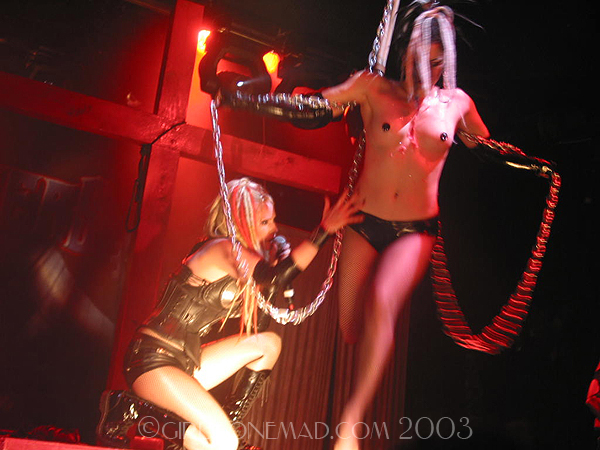 Photo of the Genitorturers at the Key Club in LA.  Gen is singing on the Cross Box while Brandy is suspended in front. John Schlick was the Lighting Designer for this show.